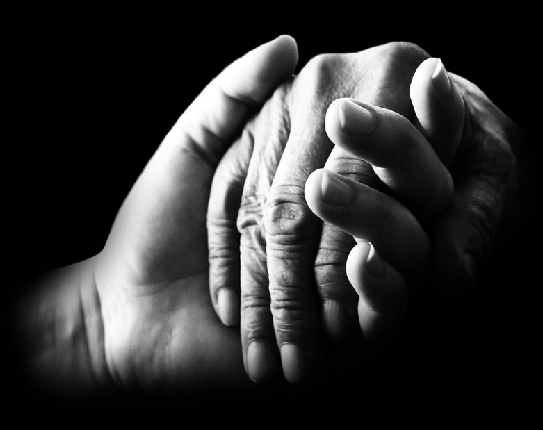Two hands holding pictured in black and white