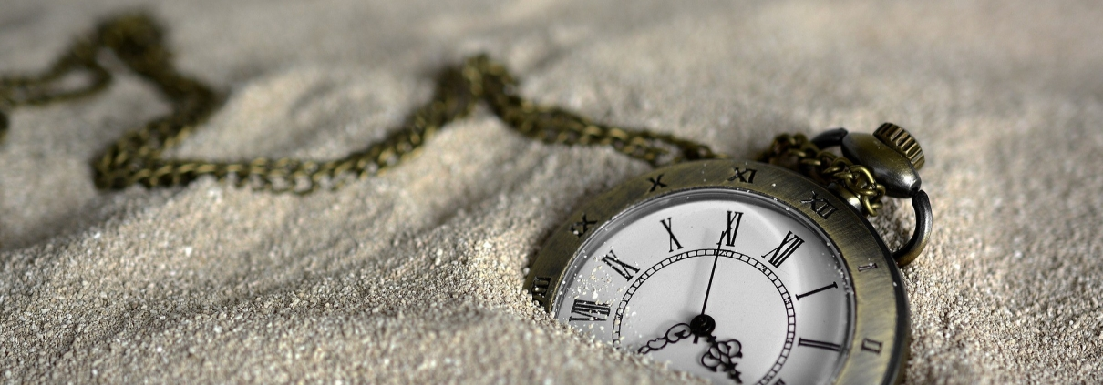 Pocket watch in the sand showing time
