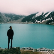 Man looking out over a lake pondering his influence