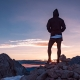 Man on rocky cliff thinking about difficult decision
